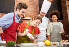 愉快的朋友和厨师在厨房里烹调烘烤 免版税库存图片