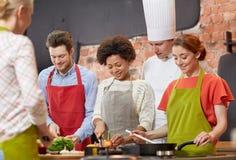 愉快的朋友和厨师在厨房里烹调烹调 免版税库存照片
