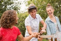 愉快的朋友在吃的公园午餐 免版税库存图片