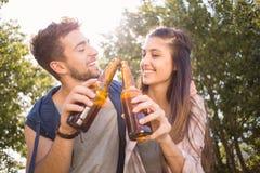 愉快的朋友在饮用的公园啤酒 免版税图库摄影