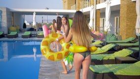 愉快的朋友女孩到有可膨胀的圆环的游泳衣里获得乐趣靠近游泳池边在夏天休假期间在手段 股票录像