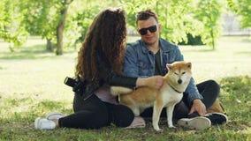 愉快的朋友女孩和人爱抚可爱的狗,谈话并且微笑着,当坐在一起佩带时的公园 影视素材
