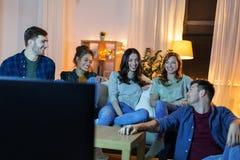 愉快的朋友看着电视在家在晚上 库存照片