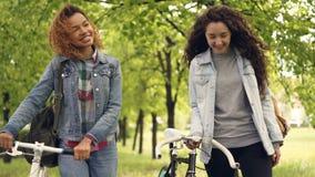 愉快的朋友美丽的妇女在快乐地谈话的公园走拿着自行车和,美丽的自然树和 股票录像