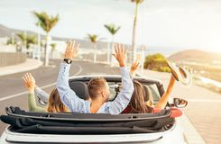愉快的朋友获得乐趣在敞篷车汽车在日落在假期-做党和跳舞在cabrio汽车的年轻人 免版税图库摄影