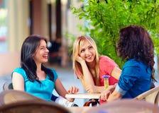 愉快的朋友谈话在夏天咖啡馆 免版税库存图片