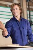 愉快的木匠与同事握手 库存照片