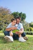 愉快的检查有放大镜的爸爸和儿子叶子 免版税库存照片