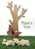 愉快的植树节,在4月种植上星期五的树问候,与木树、被雕刻的鸟、蝴蝶和绿草 库存图片
