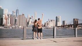 愉快的欧洲旅游夫妇跑握手胳膊被举对使曼哈顿地平线,布鲁克林大桥慢动作惊奇 股票录像