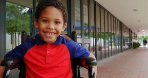 愉快的残疾非裔美国人的男小学生正面图坐在学校走廊4k的轮椅 影视素材