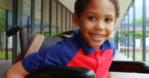 愉快的残疾非裔美国人的男小学生正面图坐在学校走廊4k的轮椅 股票视频