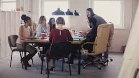 愉快的母上司主导的办公室会议 听在现代coworking的4K的经理指示的不同种族的雇员 股票视频