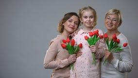 愉快的母亲、拿着郁金香灰色背景,春天假日的女儿和老婆婆 股票视频