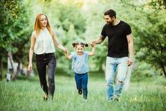 愉快的母亲、的父亲和一起跑的小女孩和获得乐趣在夏天公园 图库摄影