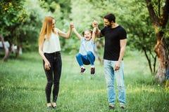愉快的母亲、的父亲和一起跑的小女孩和获得乐趣在夏天公园 免版税库存照片