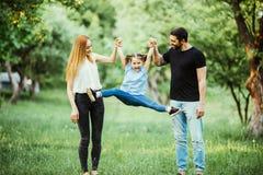 愉快的母亲、的父亲和一起跑的小女孩和获得乐趣在夏天公园 库存图片