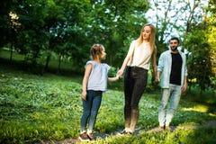 愉快的母亲、的父亲和获得的小女孩走在夏天公园和乐趣 免版税图库摄影