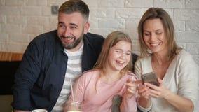 愉快的母亲、获得乐趣和采取Selfie的父亲和女孩由智能手机在咖啡馆 股票视频