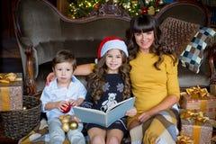 愉快的母亲、读书的小女孩和男孩 图库摄影