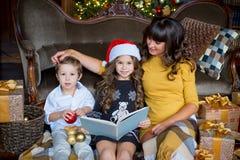 愉快的母亲、读书的小女孩和男孩 库存照片