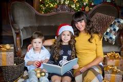 愉快的母亲、读书的小女孩和男孩 免版税库存图片