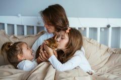 愉快的母亲和两女儿微笑的拥抱在床上 免版税库存图片