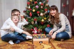 愉快的母亲和两她的儿子 婴孩圣诞节克劳斯帽子演奏s圣诞老人的母亲照片一起佩带 免版税库存照片
