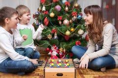 愉快的母亲和两她的儿子 婴孩圣诞节克劳斯帽子演奏s圣诞老人的母亲照片一起佩带 库存照片