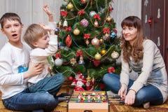 愉快的母亲和两她的儿子 婴孩圣诞节克劳斯帽子演奏s圣诞老人的母亲照片一起佩带 库存图片