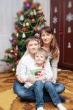 愉快的母亲和两她的儿子 婴孩圣诞节克劳斯帽子演奏s圣诞老人的母亲照片一起佩带 免版税库存图片
