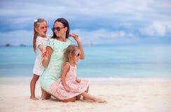 愉快的母亲和两她的在异乎寻常的海滩的孩子  免版税库存照片