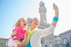愉快的母亲和做selfie的女婴在佛罗伦萨,意大利 免版税库存图片