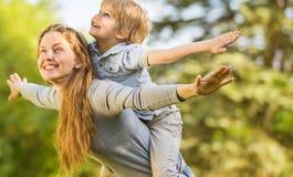 愉快的母亲和儿子在公园休息 免版税库存照片