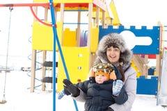 愉快的母亲和儿子在冬天装备挥动 库存照片