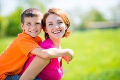 愉快的母亲和儿子室外画象 免版税库存图片