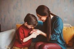愉快的母亲和儿童儿子室内画象坐长沙发和使用 免版税库存照片