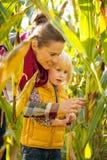 愉快的母亲和儿童探索的玉米田 免版税库存图片