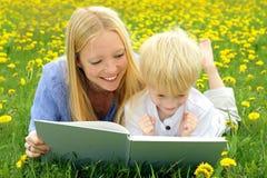 愉快的母亲和儿童阅读书外面在草甸 免版税库存照片