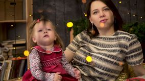 愉快的母亲和可爱的婴孩画象在用绿色云杉的分支和诗歌选装饰的屋子里 妈妈和逗人喜爱 股票视频