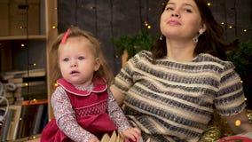 愉快的母亲和可爱的婴孩画象在用绿色云杉的分支和诗歌选装饰的屋子里 妈妈和逗人喜爱 影视素材
