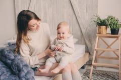 愉快的母亲和在家使用和放松在卧室的8个月大婴孩早晨 免版税库存图片