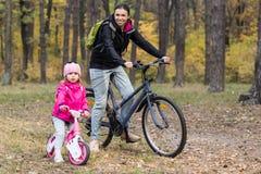 愉快的母亲和女儿乘坐的自行车 库存照片