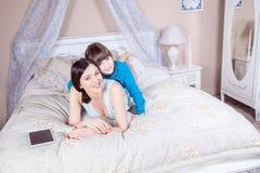 愉快的母亲和女儿在与数字式片剂的床上放置,微笑和看照相机 免版税库存图片