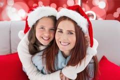 愉快的母亲和女儿在圣诞老人帽子 库存图片