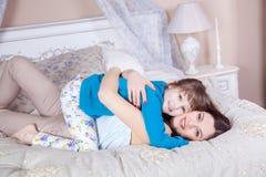 愉快的母亲和女儿在床和有乐趣上放置 免版税库存照片