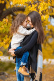 愉快的母亲和女儿在秋天的公园 免版税库存照片