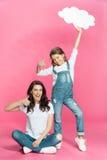 愉快的母亲和女儿有显示赞许的空白的讲话泡影的 免版税库存照片