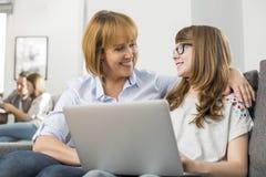 愉快的母亲和女儿有膝上型计算机的,当在家时坐在背景中的家庭 免版税库存照片