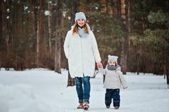 愉快的母亲和女儿步行的在冬天森林里 图库摄影